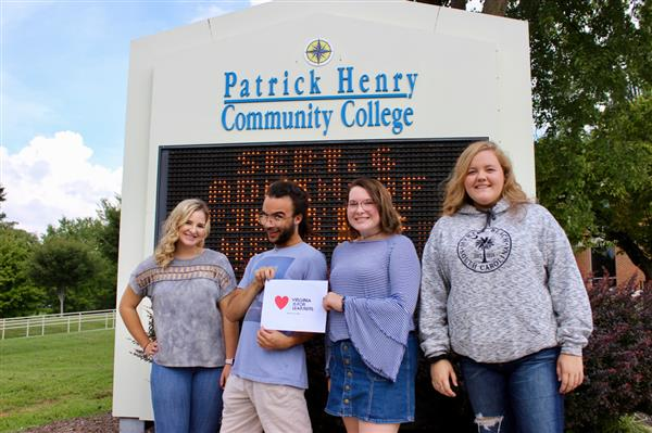 students standing in front of PHCC sign