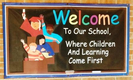 Sign with children raising their hands and the caption reading Welcome to STE!