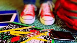 Red shoes surrounded by pens, pencils, notebooks, and tablets.