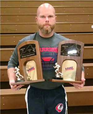 Coach Lowery holding the 2014 & 2015 State Championship football trophies.