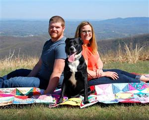 Sarah Martin, her husband Tommy, and puppy Marley on a blanket at Rocky Knob, VA